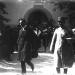 Regina Maria împreună cu Mihail Manoilescu ieșind dintr-un pavilion neidentificat (Mine, Produse Alimentare, Diverse); în jurul lor alte oficialități