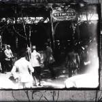 """(după o fotografie) Regele Ferdinand și alți oficiali la intrarea unui pavilion având inscripția """"Fabrica de săpun pentru toilette și medicinale S. U. Cluj - HEINRICH"""""""