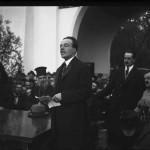 Mihail Manoilescu, comisarul general al Expoziției-Târg, ținând un discurs în cadrul Expoziției, în fața Pavilionului Petrolul (?). În dreapta lui, Mitropolitul Miron Cristea